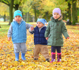 Funny kids walking in yellow foliage. Autumn in the city park.