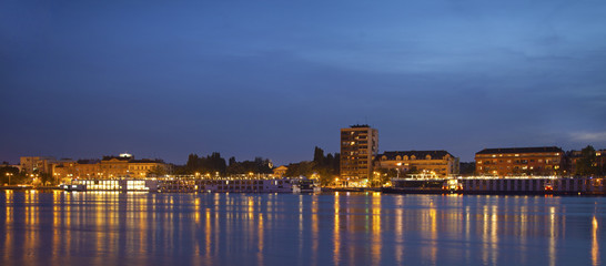 Panorama of Novi Sad quay at night with many ships docked.
