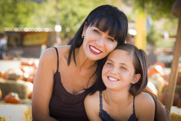 Attractive Mother and Daughter Portrait at the Pumpkin Patch.