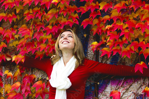Beautiful woman between red leaves - autumn