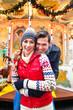 Paar kuscheln auf Weihnachtsmarkt zur Adventszeit