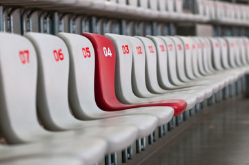 rows of white and red chairs on football stadium