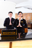 Chinese Asian reception team at hotel front desk