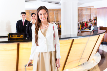 Asian Chinese woman arriving at hotel front desk