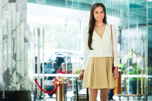 Asian Chinese Woman at hotel entrance arriving