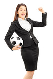 Euphoric businesswoman holding a soccer ball and gesturing