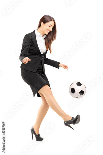 Full length portrait of a businesswoman kicking a ball
