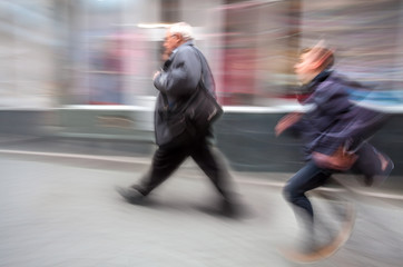 Running boy and an elderly man walking along the street