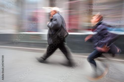 Running boy and an elderly man walking along the street