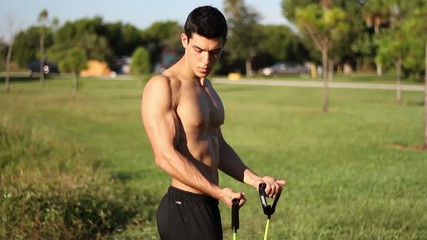 muscular young man doing arm exercises with a resistance band