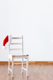 Santa claus hat hanging on empty wooden chair
