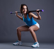 Smiling sporty woman crouches with fitbar