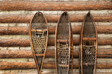 Snow shoes and a log cabin - 57466334