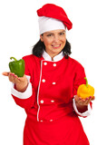 Happy chef female holding bell peppers