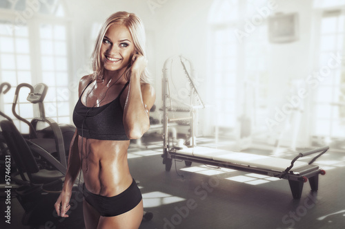 Sexy girl with headphones relaxing in the gym