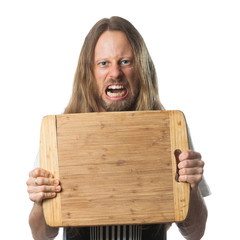 Angry man holding chopping board with copy-space.
