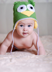 happy newborn baby  in a hat with an owl