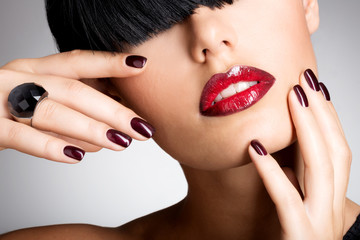 Closeup face of a woman with beautiful sexy red lips and dark na