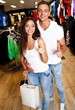 Happy young couple with shopping bag in sportswear store