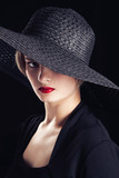 Beautiful blonde woman in black wide hat