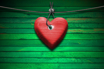 Red Wooden Heart on Green Wood Background