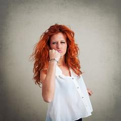 Satisfied redhead woman portrait against grunge background.