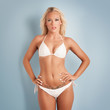 Sensual blonde woman portrait with white bikini on blue backgrou