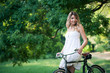 Beautiful young woman portrait with bicycle in a park.
