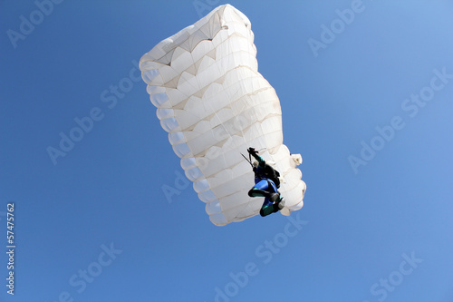 parachutist with white parachute on blue sky