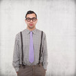 Portrait of young nerd with eyeglasses isolated on grunge backgr