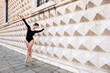 Young beautiful ballerina dancing outdoors in front of Palazzo d