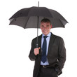 business man stands under umbrella