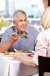 Elderly man listening to wife in restaurant