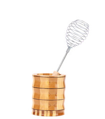 Whisk in wooden jar.