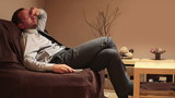 Businessman taking nap on sofa while watching tv in home