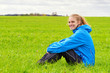 Young, sporty woman sitting on a meadow