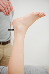 Doctor checking the reflexes of the ankle of a patient