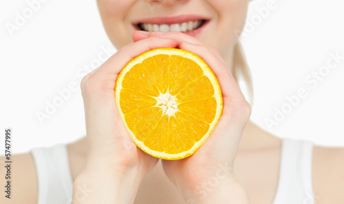 Close up of a woman holding an orange