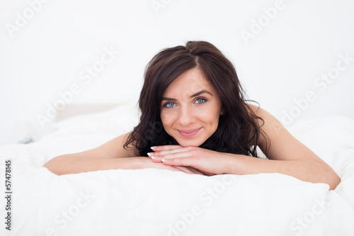 Brunette woman lying on her white duvet