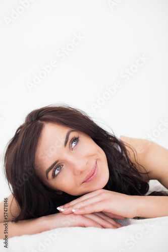 Calm woman lying on her white duvet