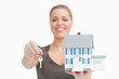 Woman blurred showing a model house and a key