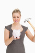 Serious woman with a piggy bank and a hammer
