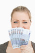 Woman hiding a middle of her face with euro banknotes