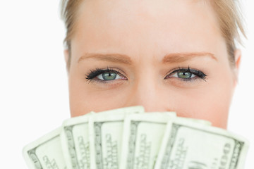 Close-up of a woman face hidden with dollars banknotes