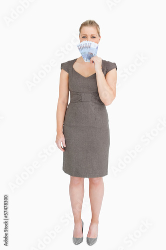 Woman hiding her mouse with euro banknotes