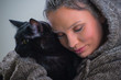 Winter portrait of young kind woman holding big black cat