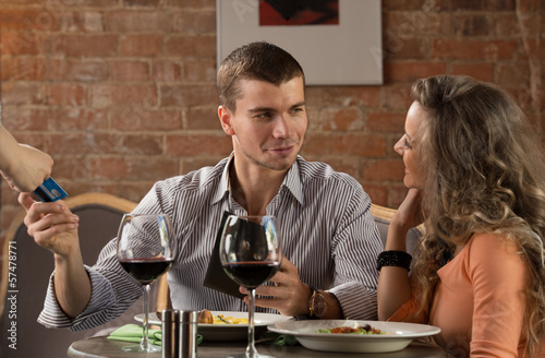 Happy couple in restaurant pay for their meal