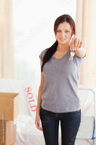 Portrait of a redheaded woman holding keys