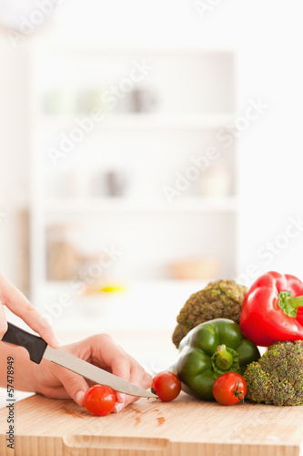 Woman's hands slicing tomatoes