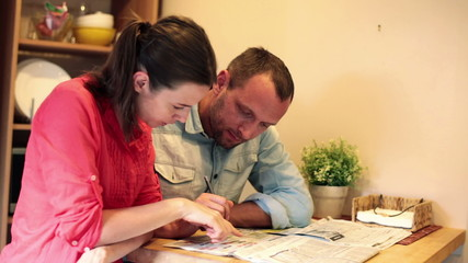 Young couple reading ads in newspaper at home